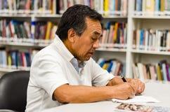 Starszego mężczyzny obsiadanie w bibliotece pisze w notepad obrazy royalty free