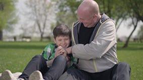 Starszego m??czyzny obsiadanie z jego wnukiem na koc w parku, ?askotanie ch?opiec Dziecko jest roze?miany leisure zbiory