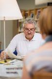 Starszego mężczyzna czytelnicza gazeta z żoną w bibliotece Zdjęcia Stock