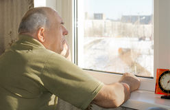 Starszego mężczyzna pozycja reminiscing przy okno Fotografia Royalty Free