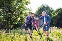 Starszego ojca naprawiania rowerowy dziurawienie n słoneczny dzień i zdjęcia stock