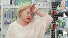 Starszej kobiety czuciowa choroba, szuka medycynę przy lokalną apteką zbiory wideo