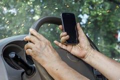Starszej kobiety napędowy samochód i dzwonić telefon komórkowy Zdjęcie Royalty Free