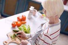 Starszej kobiety tnący ogórki w kuchni zdjęcie stock