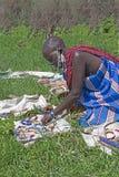 Starszej osoby Massai kobieta sprzedaje handmade z paciorkami biżuterię na koc w Tanzania, Afryka obrazy stock