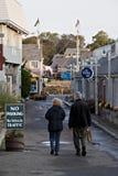 Starszej osoby para spaceruje w dół zaciszność, pusta ulica zdjęcie stock