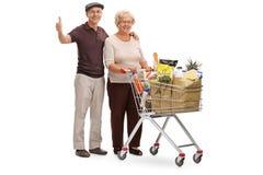 Starszej osoby para z wózek na zakupy up i kciukiem Zdjęcie Stock