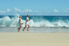 Starszej osoby pary bieg na plaży zdjęcie royalty free