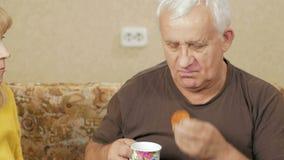 Starszej osoby pary napój herbaciany i je cukierki Mąż i żona siedzi w domu na leżance i relaksujemy wakacje domowy pojęcie zbiory