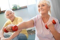 Starszej pary ćwiczenia opieki zdrowotnej mienia siedzący dumbbells uśmiecha się zakończenie wpólnie w domu Obrazy Royalty Free