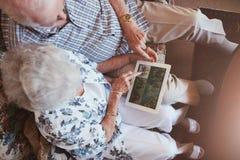 Starszej pary przyglądający wizerunki na cyfrowej pastylce zdjęcie royalty free