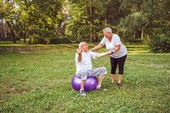 Starszy ćwiczenie - Dorośleć mężczyzny i kobieta robi wpólnie sprawności fizycznej ćwiczy na sprawności fizycznej piłce w parkowy fotografia stock