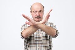 Starszy łysy mężczyzna z wąsy robi przerwie podpisywać z ręką No daję ci pozwoleniu obrazy stock