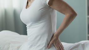 Starszy żeński obsiadanie na łóżku, naciska ręki przeciw niskiemu z powrotem, backache zdjęcie wideo