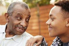 Starszy amerykanin afrykańskiego pochodzenia mężczyzna opowiada z jego młodym dorosłym wnukiem, zakończenie w górę zdjęcie royalty free