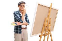 Starszy artysta pozuje obok kanwy Fotografia Stock