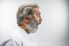 Starszy atrakcyjny mężczyzna patrzeje zaskakujący odosobnionego na bielu zdjęcia royalty free