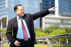 Starszy Azjatycki biznesmen uśmiecha się portret i wskazuje Obraz Royalty Free