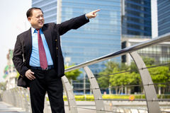 Starszy Azjatycki biznesmen uśmiecha się portret i wskazuje Obrazy Stock