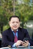 Starszy Azjatycki biznesmen używa mądrze telefon Fotografia Stock