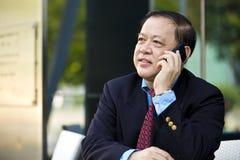 Starszy Azjatycki biznesmen używa mądrze telefon Zdjęcia Royalty Free