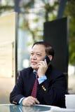 Starszy Azjatycki biznesmen używa mądrze telefon Zdjęcia Stock