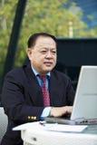 Starszy Azjatycki biznesmen używa laptopu peceta Zdjęcie Royalty Free