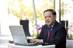 Starszy Azjatycki biznesmen używa laptopu peceta Obrazy Stock