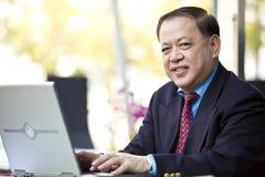Starszy Azjatycki biznesmen używa laptopu peceta Fotografia Royalty Free