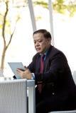 Starszy Azjatycki biznesmen używa laptopu peceta Obrazy Royalty Free
