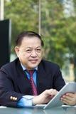 Starszy Azjatycki biznesmen używa pastylka peceta Fotografia Royalty Free