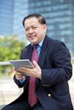 Starszy Azjatycki biznesmen używa pastylka peceta Obrazy Stock