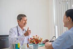 Starszy Azjatycki lekarz, aprobaty u?miech i kontakt wzrokowy z ?e?skim pacjentem obraz royalty free
