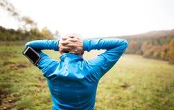 Starszy biegacz z smartphone robi rozciąganiu jesień błękit długa natura ocienia niebo zdjęcia stock