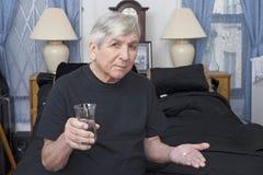 Starszy bierze lekarstwo z wodą Obrazy Royalty Free