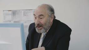 Starszy biznesmen bardzo szczęśliwy i raduje się obsiadanie przed komputerem osobistym zbiory wideo