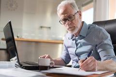 Starszy biznesmen bierze notatki, ciężki światło Fotografia Royalty Free