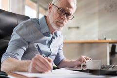 Starszy biznesmen bierze notatki, ciężki światło, lekki skutek zdjęcia stock