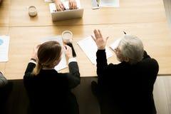 Starszy biznesmen i bizneswoman dyskutuje kontrakt rozdajemy przy obraz stock
