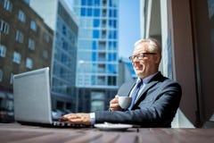Starszy biznesmen pije kawę z laptopem obraz royalty free