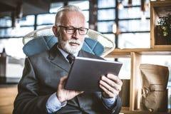 Starszy biznesmen pracuje na cyfrowej pastylce z bliska obraz stock