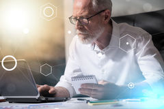 Starszy biznesmen pracuje na laptopie, lekki skutek, lekki skutek, overlayed z diagramami Obrazy Stock