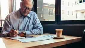Starszy biznesmen pracuje od nowożytnej kawiarni zdjęcia stock