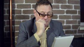 Starszy biznesmen w eyeglasses pracuje z cyfrową pastylką przy biurem zbiory wideo