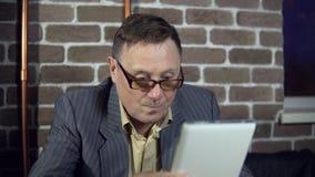 Starszy biznesmen w eyeglasses pracuje z cyfrową pastylką przy biurem zdjęcie wideo