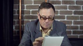 Starszy biznesmen w eyeglasses pracuje z cyfrową pastylką przy biurem zbiory