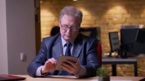 Starszy biznesmen w formalnym kostiumowym obsiadaniu przed laptopem pracuje z pastylką jest baczny w biurze zbiory