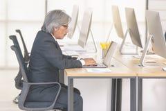 Starszy biznesmen w kostiumu obsiadaniu w nowożytnym biurze dalej i pracie zdjęcia stock