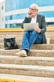Starszy biznesmen z laptopu mówieniem na smartphone obrazy stock