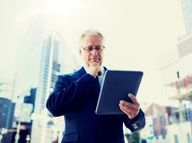 Starszy biznesmen z pastylka komputerem osobistym na miasto ulicie fotografia stock